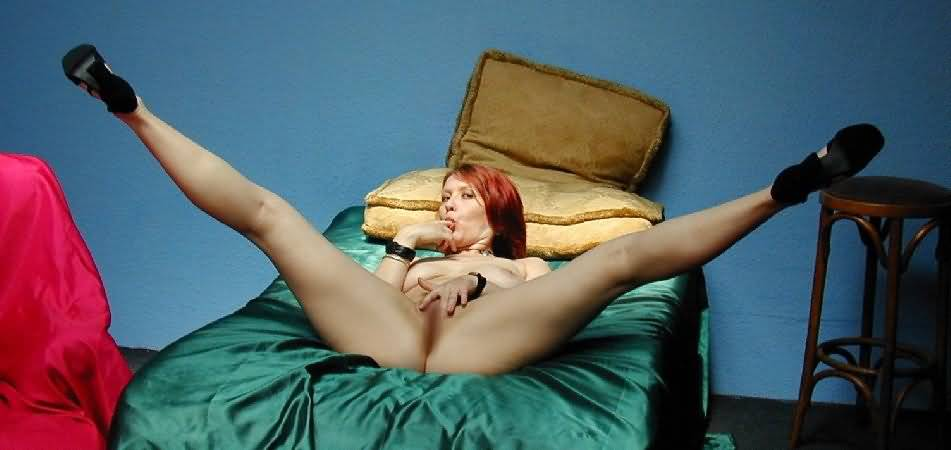 Fanella with legs spread as wide as she can get them, holding her pussy open